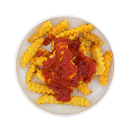 small plate: Top view of crispy French fries covered with ketchup in a small plate isolated on a white background.