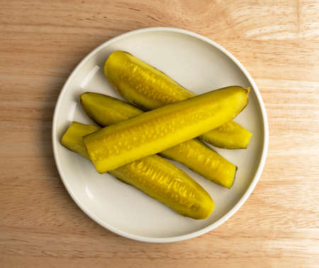 small plate: Top view of several bread and butter pickle spears on a small plate atop a wood table top illuminated by window light. Stock Photo