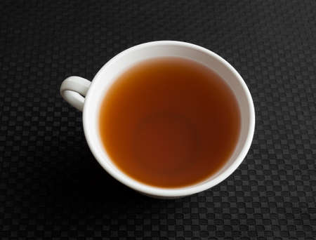 green and black: A cup of passion fruit green tea atop a black tablecloth. Stock Photo