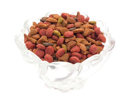 cat food: A glass bowl filled with generic dry cat food isolated on a white background.