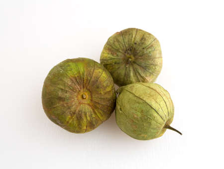 husk tomato: Three ripe tomatillos on a white cutting board illuminated with natural light.
