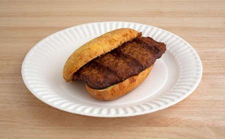 pork rib: Un panino costola di maiale con salsa barbecue su un piatto di carta bianca sulla cima di un tavolo di legno.