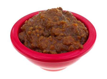sloppy: A small red bowl filled with beef and barbecue sauce sloppy joe mix on a white background.