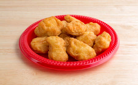 Chicken Nuggets: A serving of chicken nuggets on a red plate on a wood table top illuminated with window light.