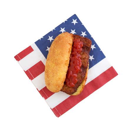pork rib: Un panino costola di maiale con ketchup su un rosso bianco e blu tovagliolo patriottica isolato su uno sfondo bianco. Archivio Fotografico