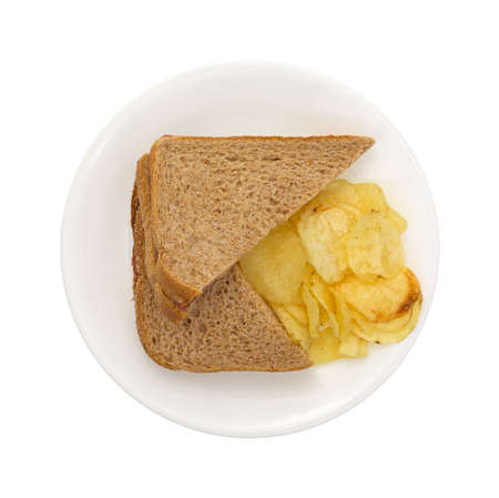 inexpensive: Top view of a whole wheat sandwich with potato chips on a white plate.