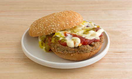 sesame seed bun: A cheeseburger with sesame seed bun plus mayonnaise, ketchup and relish on a small plate atop wood table.