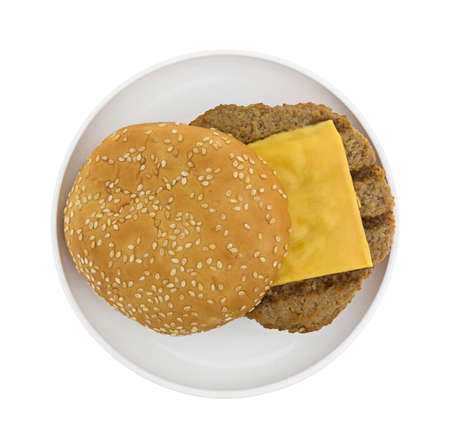sesame seed bun: Top view of a microwaved cheeseburger with sesame seed bun on a small plate atop a white background.