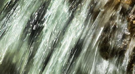 Close view of fast moving water over rocks with an abstract look.