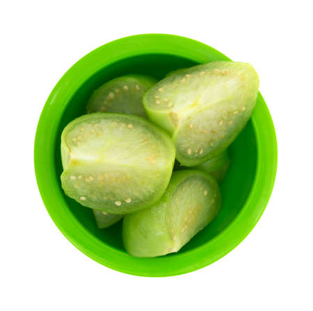 husk tomato: Top view of several sections of cut tomatillos in a small green dish isolated on a white background.