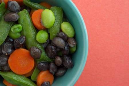 buttered: Close view of buttered carrots, black beans, edamame and snap peas in a bowl atop an orange background.