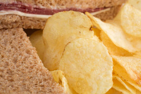 Close view of a roast beef wheat bread sandwich with white cheese and mayonnaise plus potato chips.