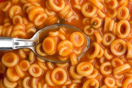 pasta sauce: A very close view of canned round spaghetti pasta with tomato sauce in a spoon illuminated by natural light.