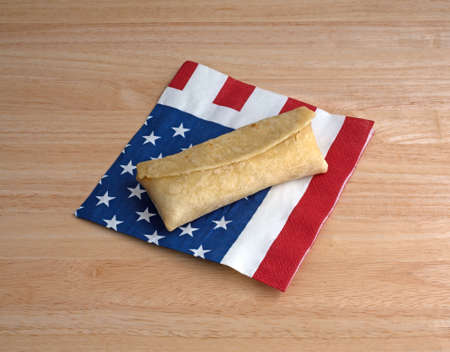 atop: A microwaved chicken and cheese chimichanga on a flag motif napkin atop a wood table top.