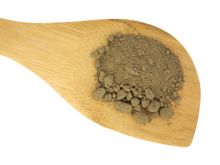 A large wood spoon with a portion of comfrey root powder on a white background. Stock Photo