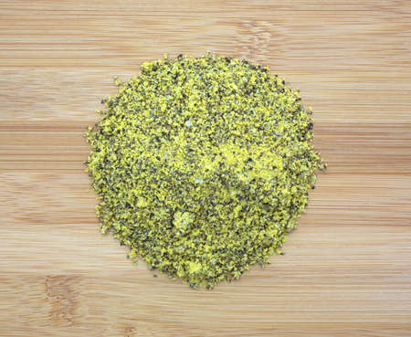 Top view of a small portion of lemon pepper seasoning on a wood cutting board. Фото со стока