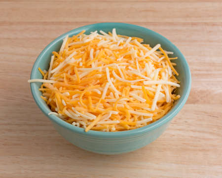 mild: A small bowl filled with shredded white cheddar, sharp cheddar and mild cheddar cheeses atop a wood table top. Stock Photo