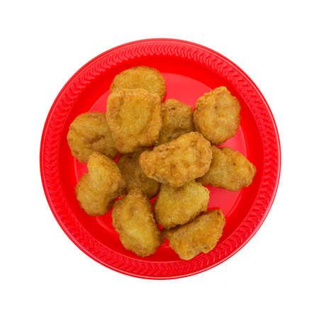 nuggets pollo: Vista superior de una porci�n de nuggets de pollo en un plato rojo aislado en un fondo blanco. Foto de archivo