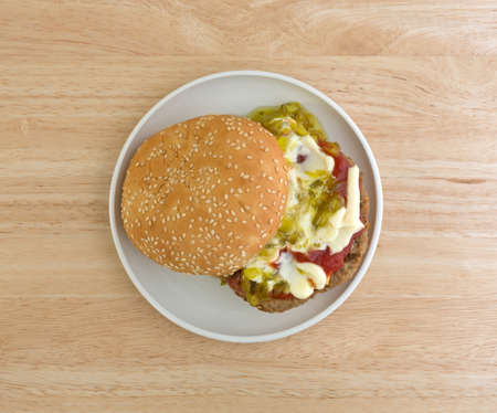 sesame seed bun: Top view of a cheeseburger with sesame seed bun plus mayonnaise, ketchup and relish on a small plate atop wood table. Stock Photo