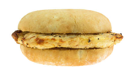 Side view of a microwaved previously grilled chicken breast sandwich on a white bread bun isolated on a white background. Stock Photo