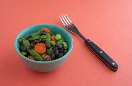 buttered: Assorted buttered cooked vegetables in a small bowl with a fork to the side on an orange background illuminated by natural light. Stock Photo
