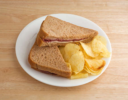 A roast beef wheat bread sandwich with white cheese and mayonnaise plus potato chips on a white plate atop a wood table top.