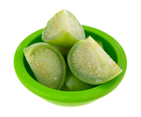 husk tomato: Several sections of cut tomatillos in a small green dish isolated on a white background.