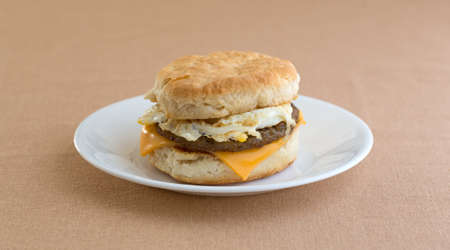 A sausage egg and cheese biscuit breakfast sandwich on a white plate upon a tan table cloth.
