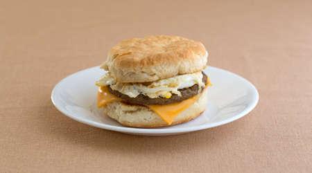 Een worstei en kaaskoekjesontbijtsandwich op een witte plaat op een tan lijstdoek. Stockfoto
