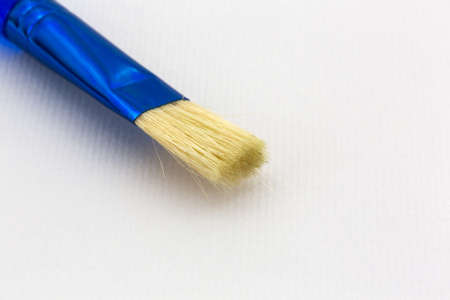 handled: Close view of a blur handled bristle brush atop textured watercolor paper.