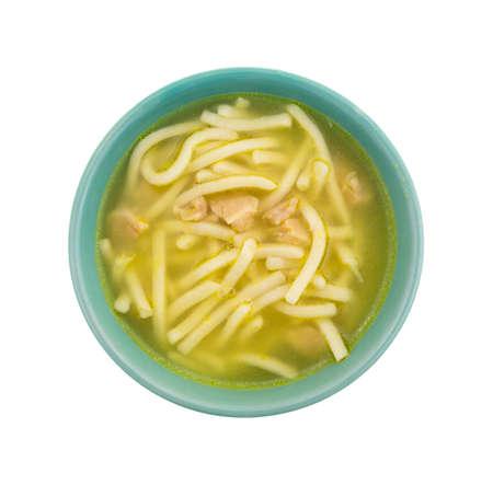 sopa de pollo: Vista superior de un pequeño tazón verde con una porción de sopa de fideos de pollo aislado en un fondo blanco.