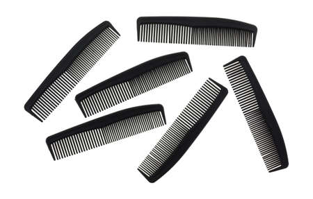 inexpensive: Several small black plastic barber shop combs isolated on a white background