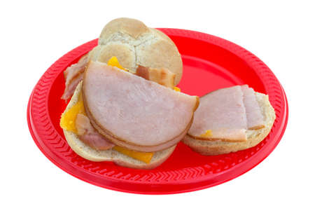 cheddar cheese: Side view of small turkey sandwiches with bacon and cheddar cheese open on a red picnic plate.