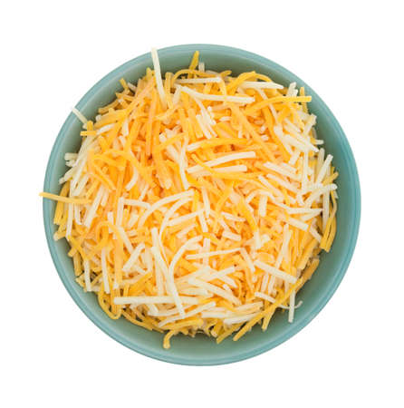 Top view of a small bowl filled with shredded white cheddar, sharp cheddar and mild cheddar cheeses isolated on a white background.
