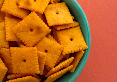 atop: Top close view of a bowl of cheese crackers atop an orange background illuminated with natural light. Stock Photo