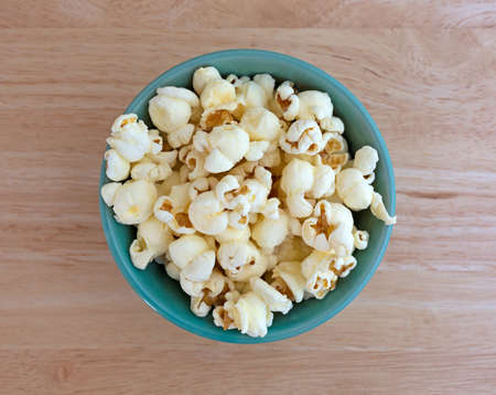 bowls of popcorn: Top view of a small bowl filled with a serving of white cheddar cheese flavored popcorn on a wood table top illuminated with natural light.