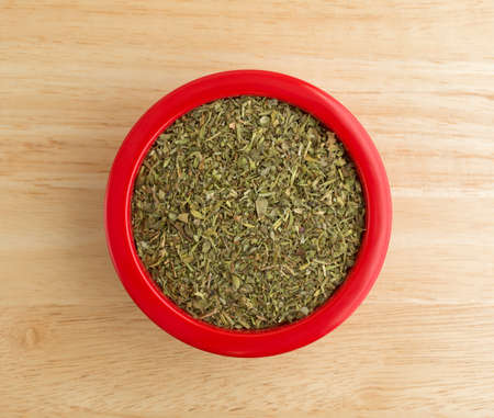 Top view of a red dish filled with Italian seasoning on a wood counter top illuminated with natural light.