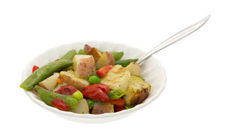 red peppers: A bowl of roasted potatoes, snap peas and red peppers in a garlic sauce with a fork inserted into the food on a white background. Stock Photo