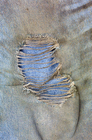muddy clothes: Close view of a ragged hole in muddy worn blue jeans.