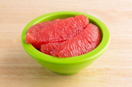 dieta sana: Secciones de pomelo rojo en un plato verde sobre una mesa de madera.