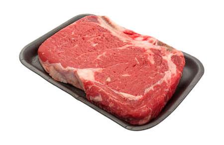 rib eye: A large bone in rib eye steak on a black butcher tray isolated on a white background. Stock Photo