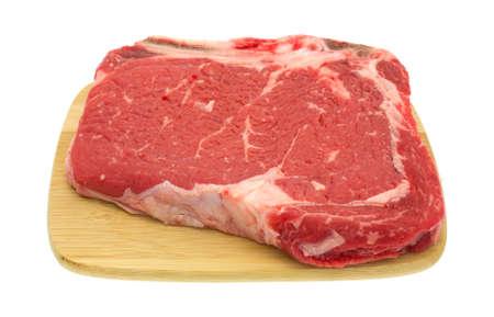 rib eye: A large bone in rib eye steak on small wood cutting board isolated on a white background.