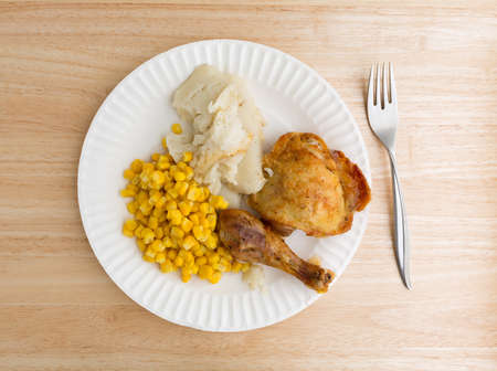 tines: Top view of roasted chicken, mashed potatoes and corn on a white paper plate with a fork to the side atop a wood table top.