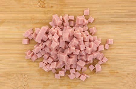 Top view of a portion of diced ham on a wood cutting board.