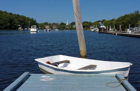 pleasure craft: A white dinghy floating at the end of a dock with boats and the distant town of Ellsworth, Maine in the summertime. Stock Photo