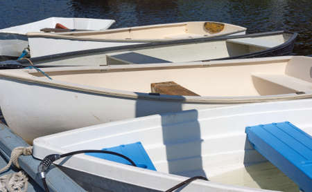 dinghies: A group of small dinghies tied to a town dock. Stock Photo