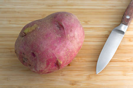 organically: An organically grown red potato on a cutting board with a kitchen knife illuminated with natural light. Stock Photo