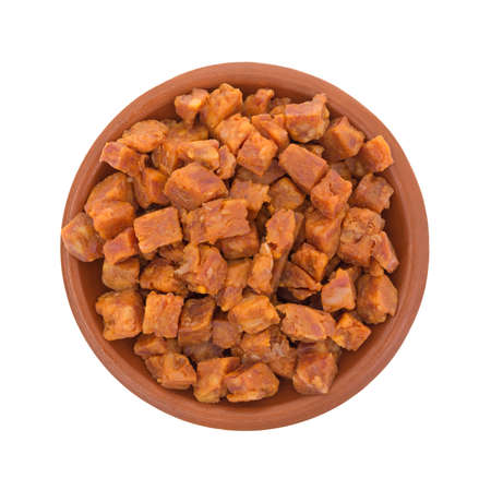 Top view of a small bowl of pepperoni pizza topping that has been chopped into small cubes isolated on a white background.