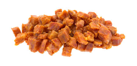 Pepperoni pizza topping that has been chopped into small cubes isolated on a white background. Stock Photo