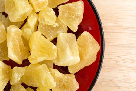 chunks: Top close view of a serving of dried sugared pineapple chunks on a red dish atop a wood table top.